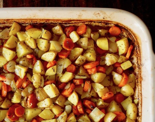 Chopped roasted potatoes, carrots and onions in baking dish.
