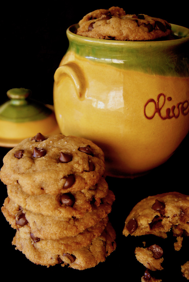 Large golden, ceramic container with the word olive written on it, with a small stack of olive oil chocolate chip cookies next to it.