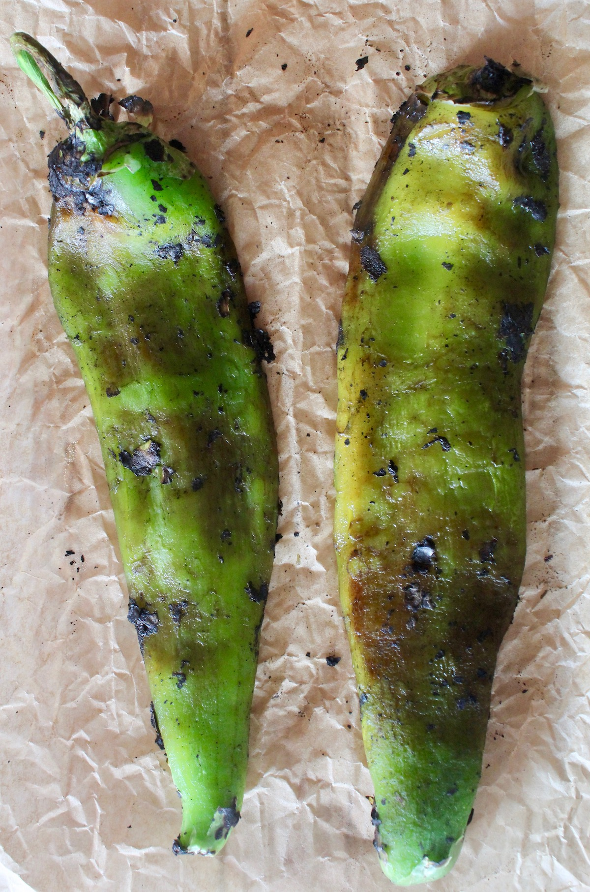 two roasted and peeled hatch chiles on parchment
