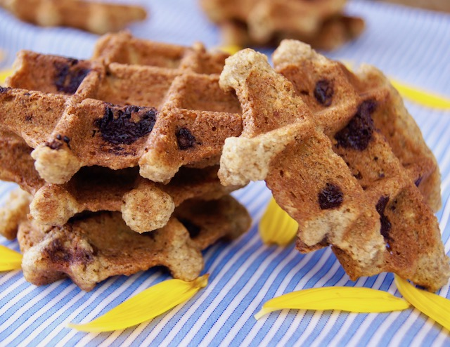 Four stacked Waffle Cookies with chocolate and pecans on a blue cloth.