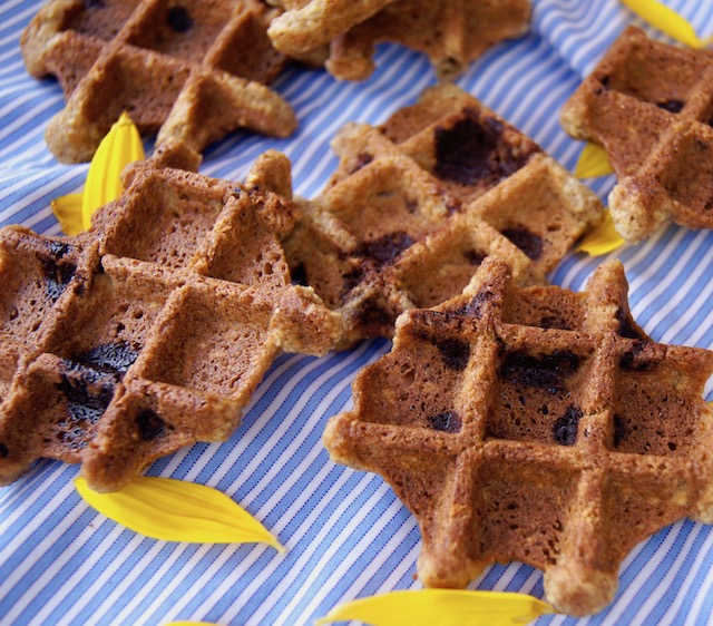 A few Waffle Cookies with Chocolate and Pecans spread out on a light blue cloth.