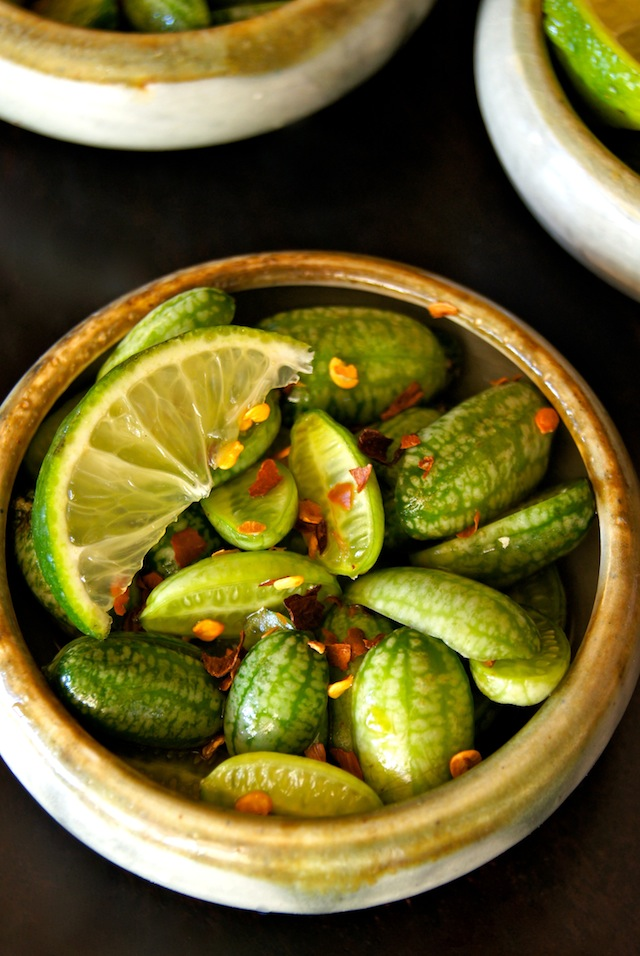 Small bowl with cucamelons, chili flakes and lime wedge