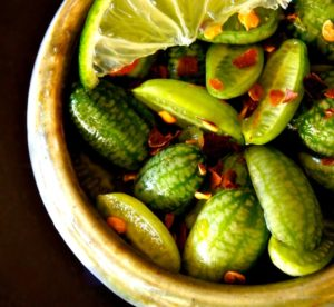 close up of cucamelons in a beige bowl with chili flakes and lime