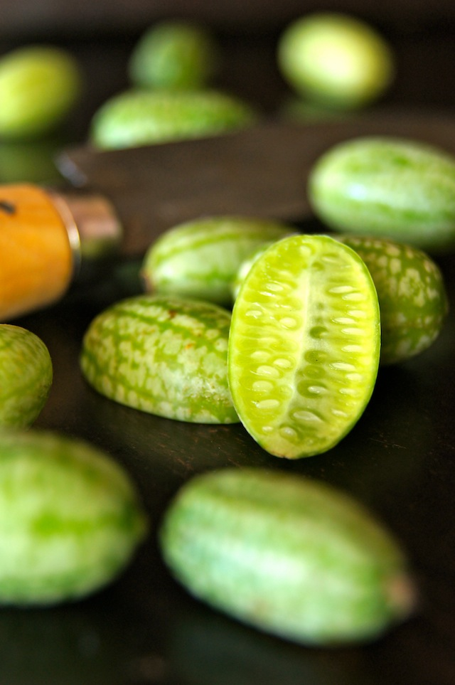 several cucamelons with a knife and one sliced in half