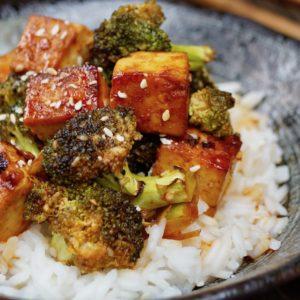 Sesame Sriracha Honey Tofu Broccoli in a black bowl with wooden chopsticks.
