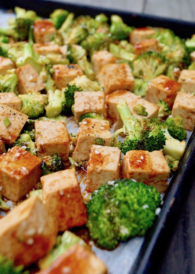 Tofu cubes and broccoli on a sheet pan dirzzled with Sesame Sriracha Honey marinade