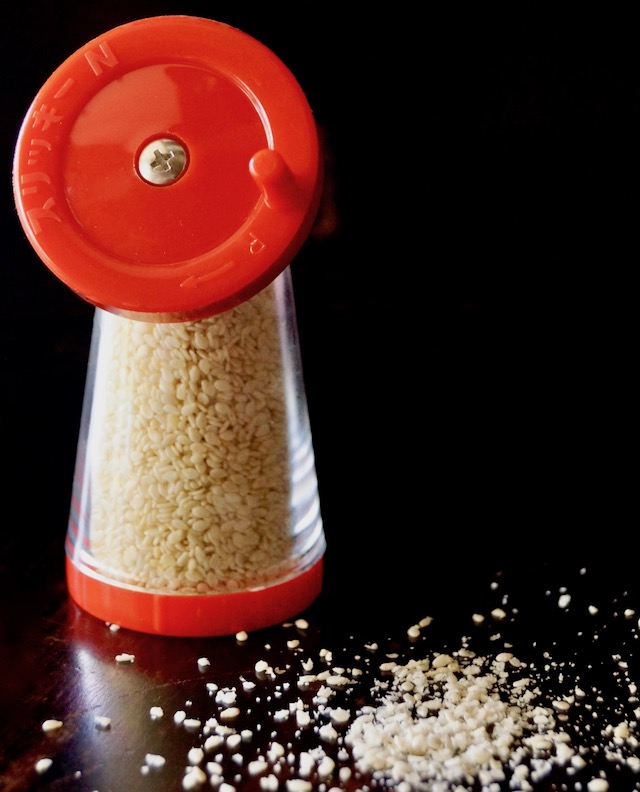 Red sesame seed grinder on black background with ground seeds next to it.