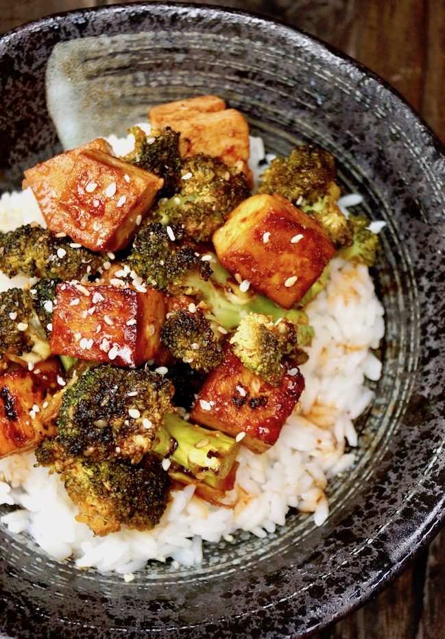 Sesame Sriracha Honey Glazed Tofu Broccoli over white rice in a black. bowl.