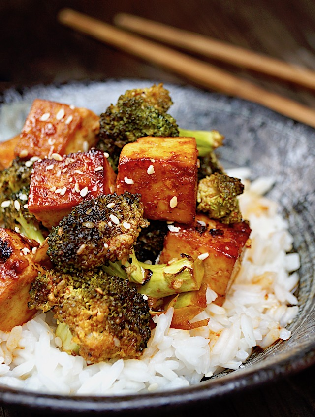 Sesame Sriracha Honey Tofu Broccoli in a black bowl with wooden chopsticks.