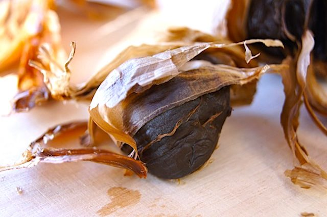 one clove of black garlic with skin coming off