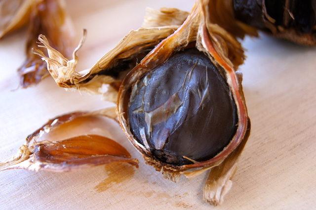 black garlic clove halfway unpeeled