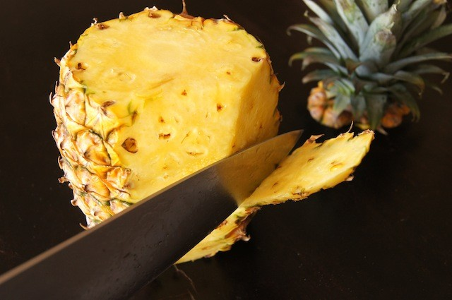 Pineapple being peeled with a large chef's knife