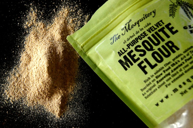 Bag of mesquite flour with some spilled out onto dark table.