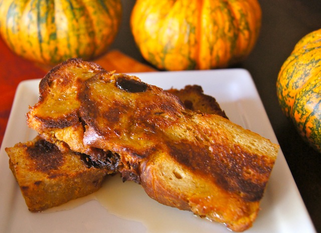 2 slices of Maple Pumpkin Chai-Bread French Toast on a square white plate with pumpkins behind it.