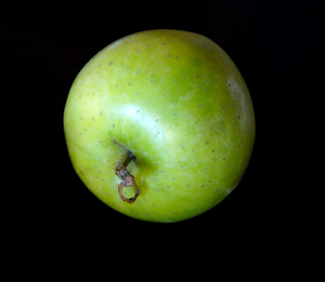 One Green Dragon Apple on a black background.
