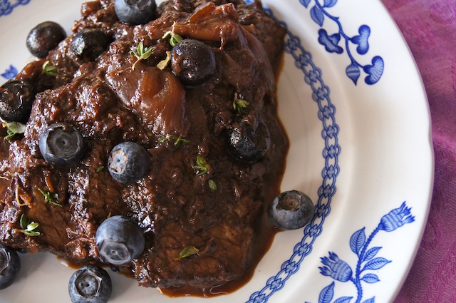 Blueberry Balsamic Braised Brisket on a white and blue plate with fresh blueberries