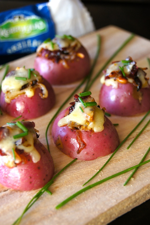 Several Cheddar Potato Bites with Cranberry Pecan Onions on a cutting board.