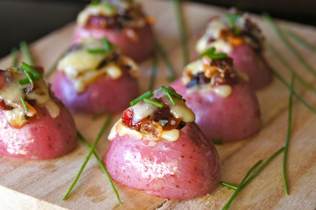 Six Mini Red Potato Appetizer with Cranberries on light cutting board with chives.