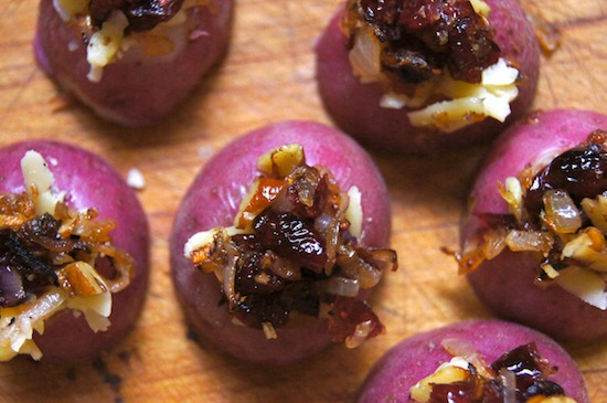 Mini red potatoes with caramelized onions on cutting board