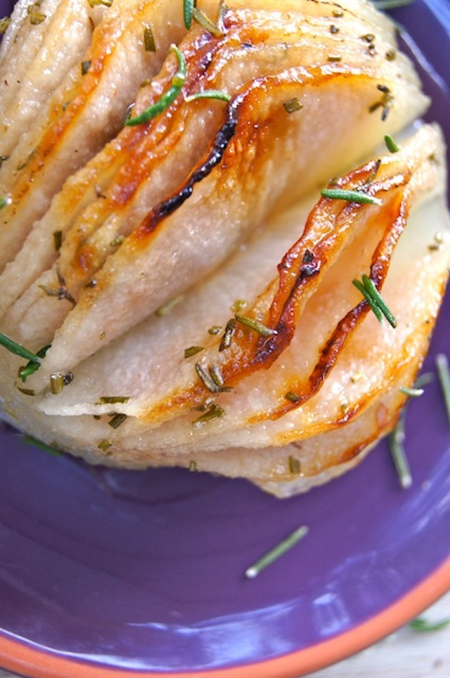 close up of a Rosemary Roasted hasselback Korean Pear with fresh rosemary leaves