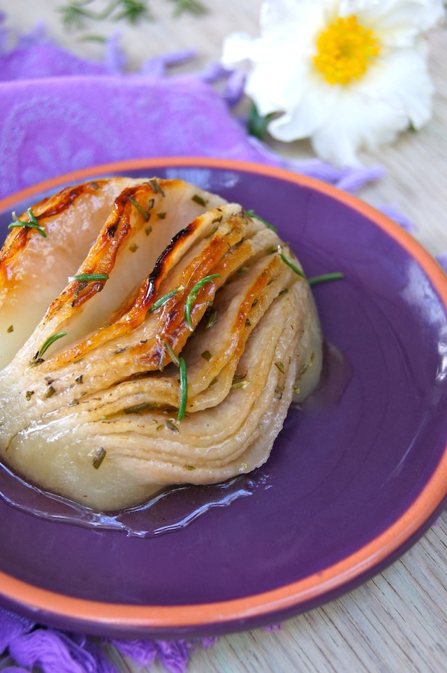 Rosemary Roasted Hasselback Korean Pear on a purple plate with fresh rosemary leaves