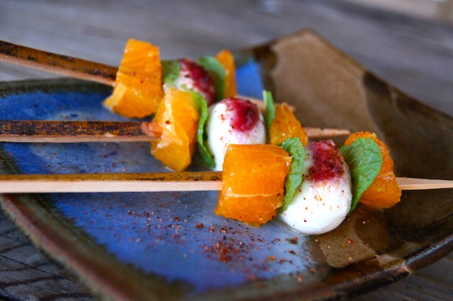 Citrus Caprese Kebabs on a ceramic blue and beige, square dish