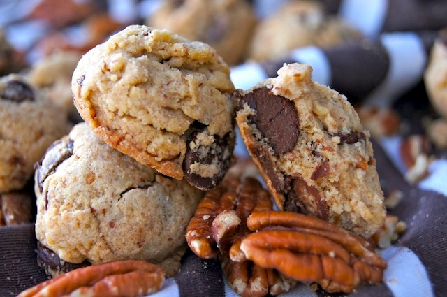 Small pile of Pecan Praline Chocolate Chip Cookies with raw pecans