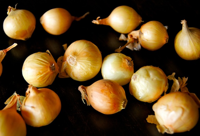 golden pearl onions on black background