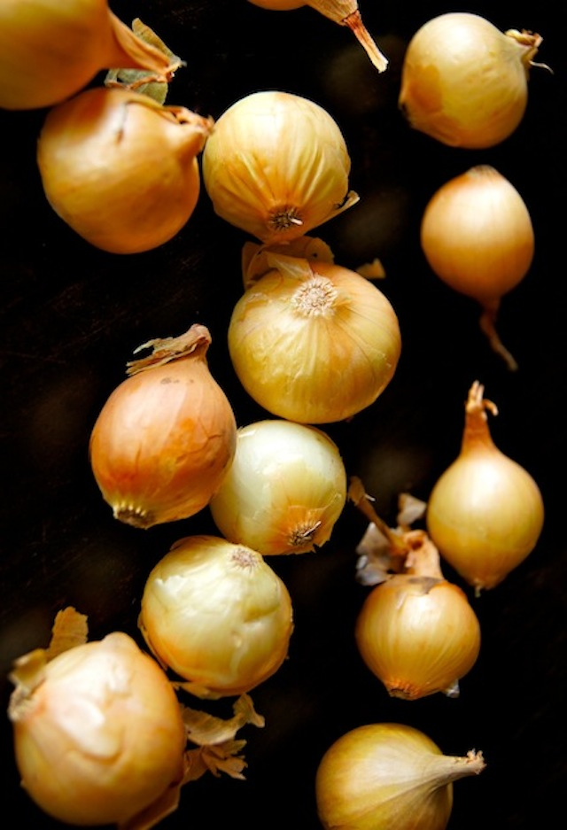 many pearl onions with yellow-orange peels on