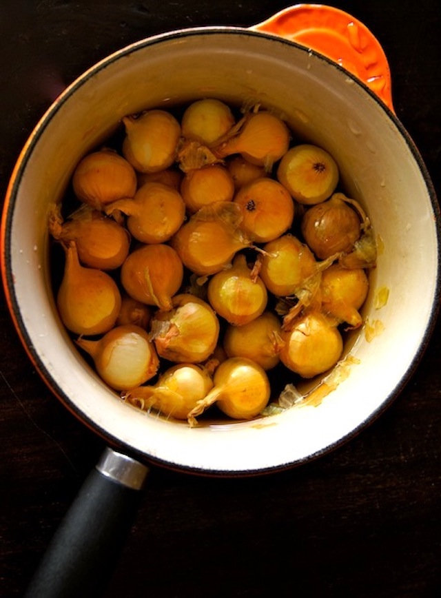 How to Easily Peel Pearl Onions - the pearl onions with yellow-orange peels still on, in a pot with water covering them