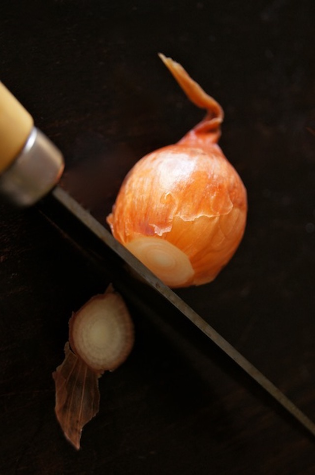 How to Easily Peel Pearl Onions - one pearl onion with orange peel, and small knife cutting off root