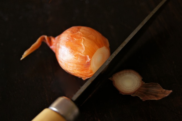 pearl onion with a paring knife cutting root end off