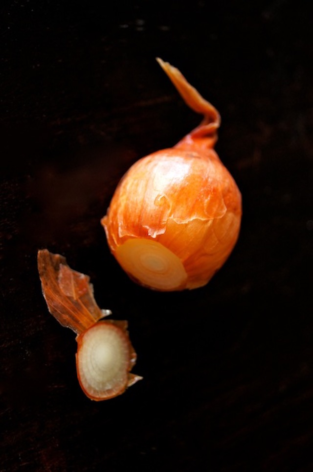 How to Easily Peel Pearl Onions - one pearl onon with orange skin and root end cut off