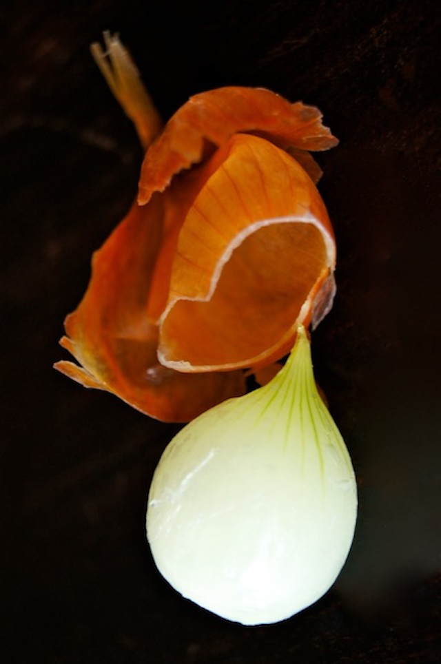 How to Easily Peel Pearl Onions - one white pearl onion with orange peel removed and next to it