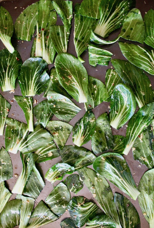 raw baby bok choy leaves on baking sheet