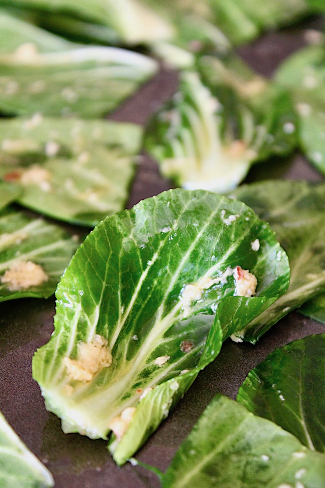 close up of raw bok choy leaf with oil and garlic