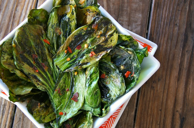 Crispy Garlic Ginger Bok Choy Chips in a white dish, sticking up over the edge.
