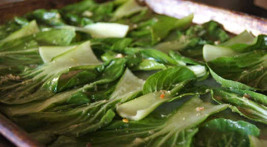 fresh bok choy leaves on a sheet pan with oil and spices