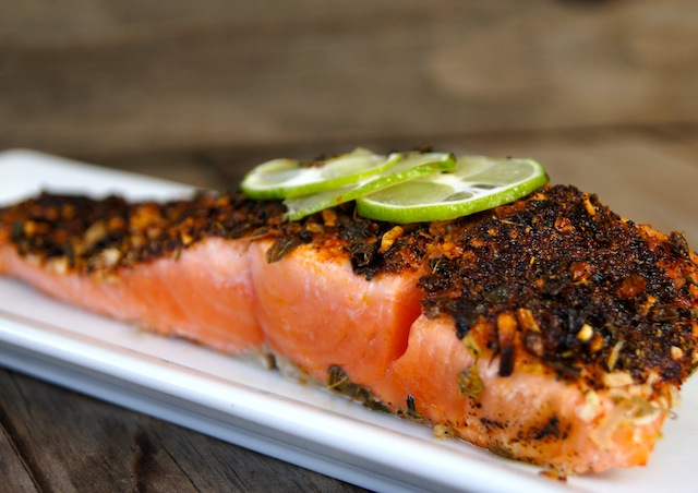 One fillet of 5-Minute Mexican Blackened Salmon on a white, narrow plate, with three thin lime slices on top.
