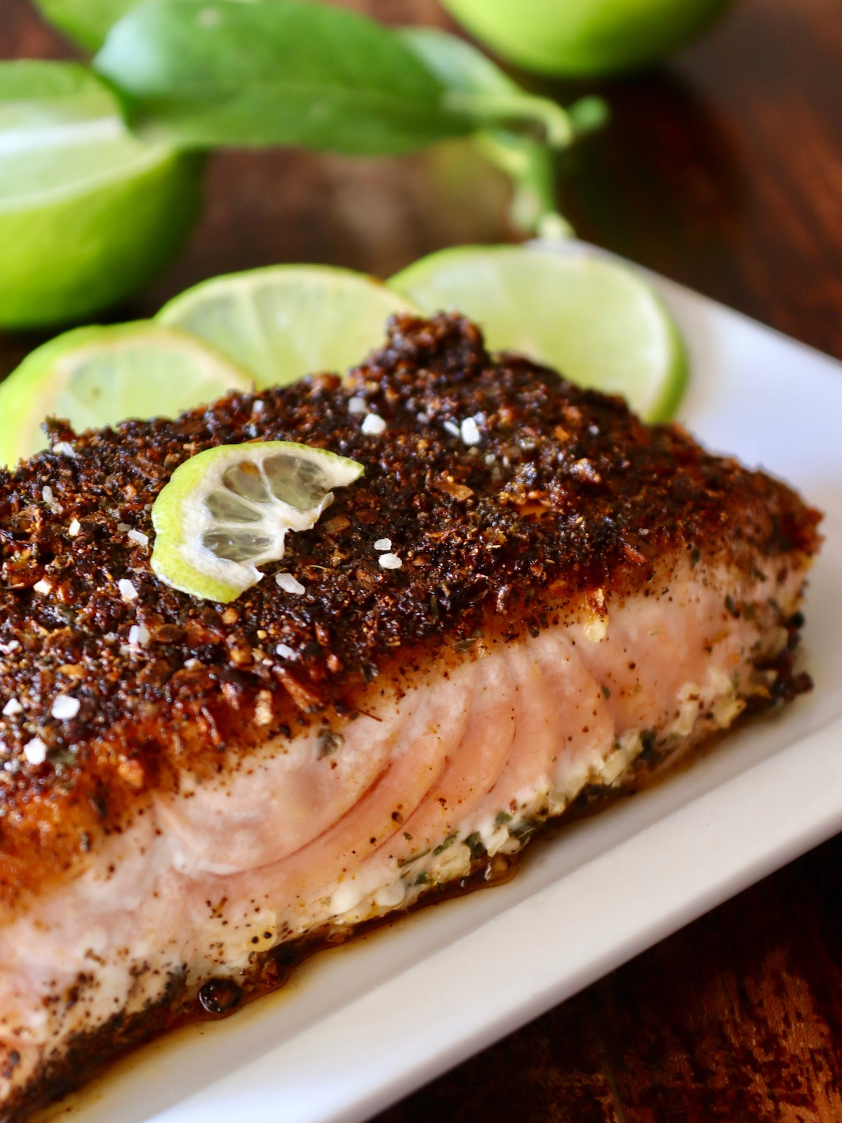 On a light wooden table, a top view of one fillet of 5-Minute Mexican Blackened Salmon presented on a narrow white plate with three lime slices on top.