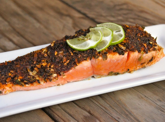 On a light wooden table, there's one fillet of 5-Minute Mexican Blackened Salmon presented on a narrow white plate with three lime slices on top.