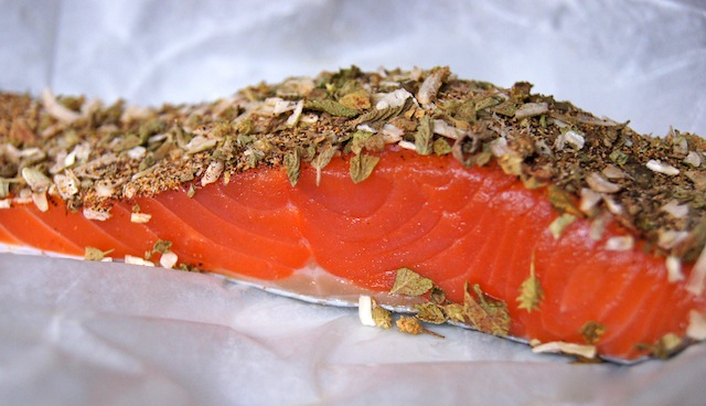 "5-Minute Mexican Blackened Salmon being prepped to cook on parchment -- the bright orange salmon is raw, and the spices, not yet ""black,"" are on the top surface of the fillet."