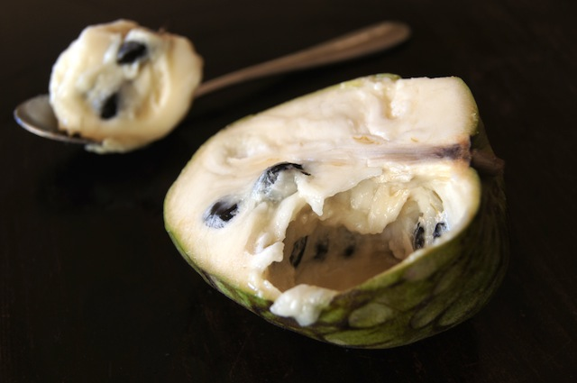 Cherimoya half with one spoonfull removed, the flesh is white and seeds are black