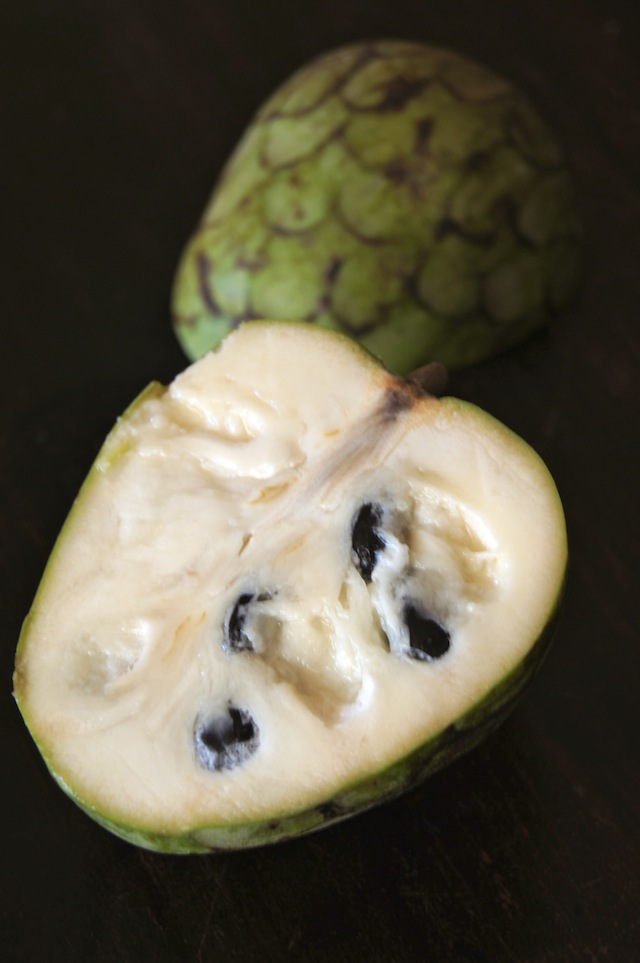 Cherimoya fruit cut in half with green skin, white flesh and black seeds