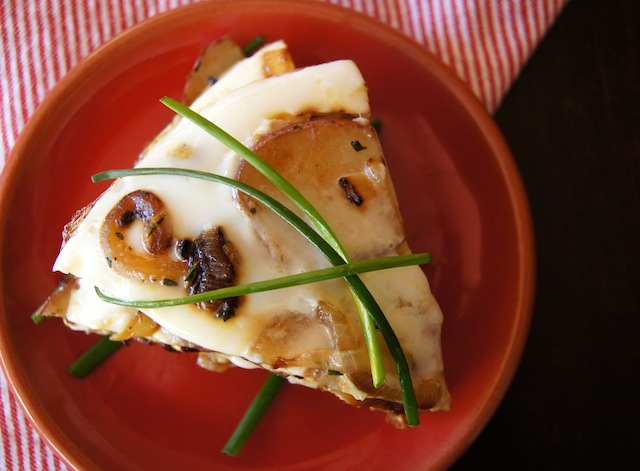 Potato Egg White Frittata, cut into two pie-shaped slices on a red plate with green chives