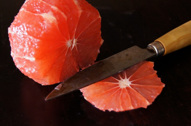 peeled citrus being cut into slices