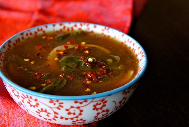gai lan soup with egg in white bowl with red floral pattern