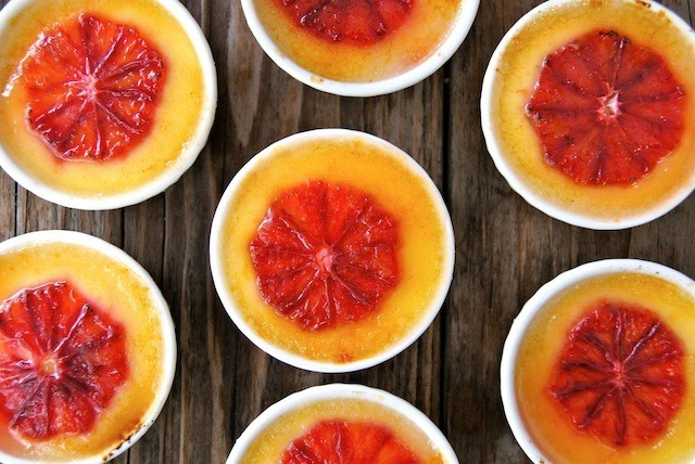 several white ramekins of Blood Orange Champagne Creme Brulee on a dark wood surface