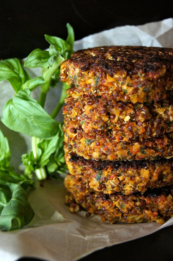 Stack of Crispy Red Quinoa Almond-Tomato Burgers with basil on parchment