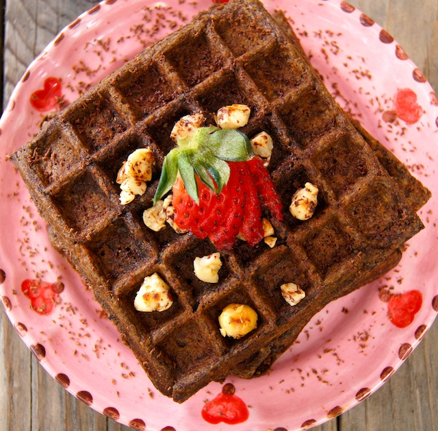 top view of Gluten-Free Chocolata Hazelnut Waffles on a pink plate with a strawberry fanned out on top